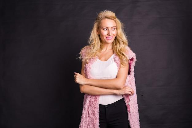 Modellering, mode, mensen concept-jonge ernstige blonde in roze jas over de zwarte achtergrond met
