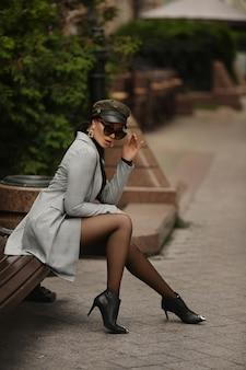 Modelmeisje met lange benen die kousen en modieuze trenchcoat dragen die op de bank zitten en in de camera kijken