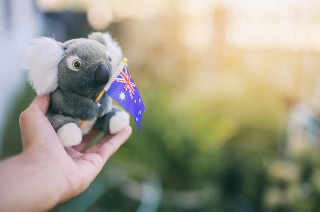 Modelmodel koala houdt australische nationale vlag vast, bid voor australië. bush bosbranden in australië.