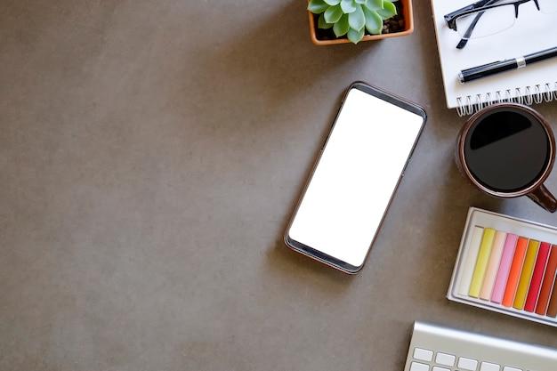 Modelsmartphone met het lege scherm op werkruimte.