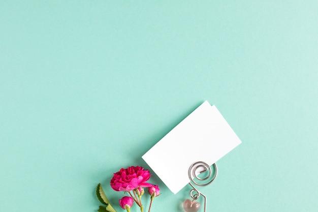 Modelvisitekaartjes op een gekleurde achtergrond en een roze bloem, copyspace, bovenaanzicht.