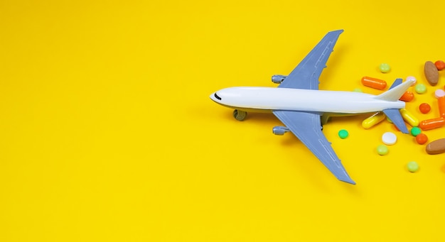 Modelvliegtuig met veelkleurige pillen van bewegingsziekte close-up op een gele achtergrond. concept ziekte in reizen.selectieve focus