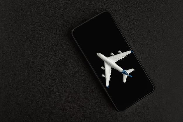 Modelvliegtuig op smartphone op zwart.
