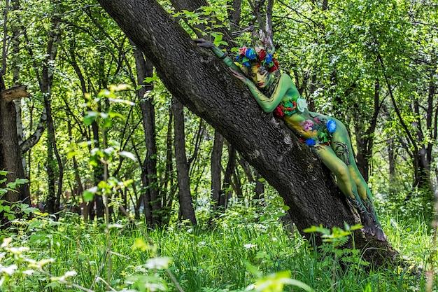 Modelvrouw in de vorm van een nimf tussen de bomen met ongebruikelijke mooie patronen op het lichaam
