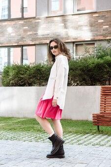 Modelvrouw in zonnebril poserend tegen de achtergrond van een stadsstraat in een nieuwe zomercollectie en kledingcatalogus