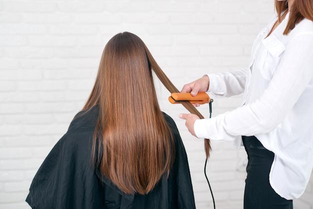 Modelzitting terwijl hairstyling in beaty salon met witte bakstenen muren.