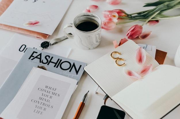 Modemagazine met koffie en bloemen