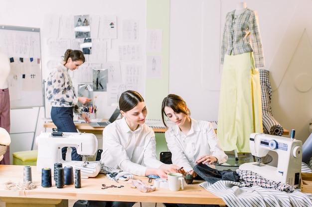 Modeontwerp, naaister, kleermaker en mode-concept. twee jonge vrouwen naaisters naaien zittend op hun werkplek. modeontwerper op de achtergrond die nieuwe modieuze stijlen creëert.
