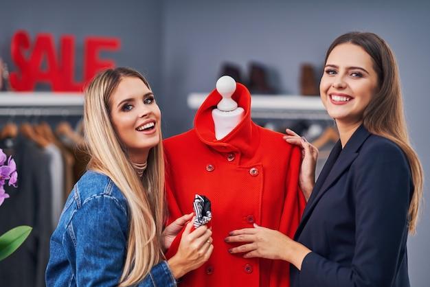 Modeontwerper die de klant bijstaat in de kledingboetiek