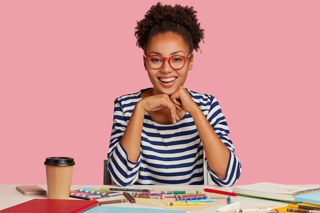 Modeontwerper met brede glimlach, voelt zich sarisfied, houdt de handen onder de kin, draagt gestreepte kleding, geïsoleerd over een roze muur. positieve schilder heeft inspiratie voor tekenen. creatief werkconcept