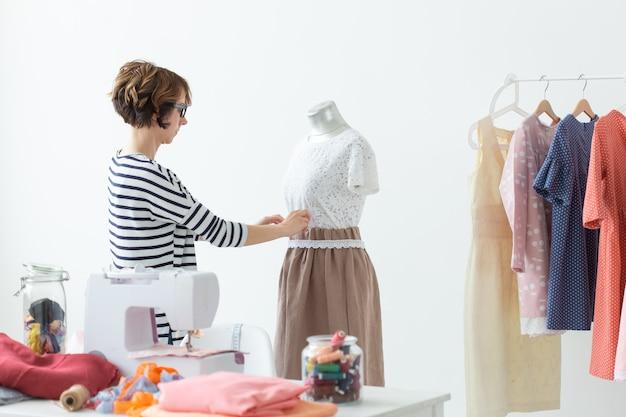 Modeontwerper, naaister en small-sized enterprises concept - vrouw naaister versiert
