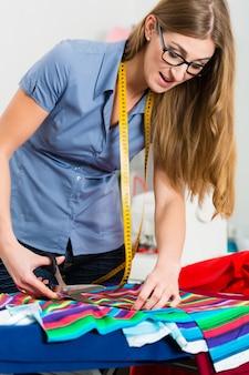 Modeontwerper of kleermaker in de studio werken