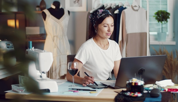 Modeontwerper schets maken met laptop in de naaiatelier