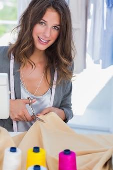 Modeontwerper snijden textiel naast een naaimachine