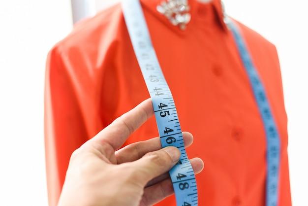 Modeontwerper studio meten van textielmateriaal schaar snijden van stof door ontwerper stijlvolle showroom - ontwerper werken professioneel meten van een jurk kleding voor het aanpassen van model vrouw in werkplaats
