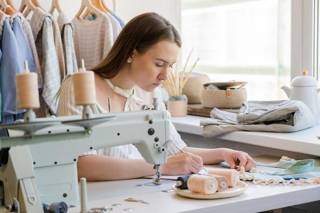 Modeontwerper tekening kleding schets terwijl ze op haar werkplek zit met naaimachine