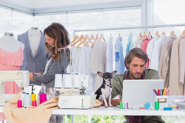 Modeontwerpers aan het werk met een puppy op het bureau