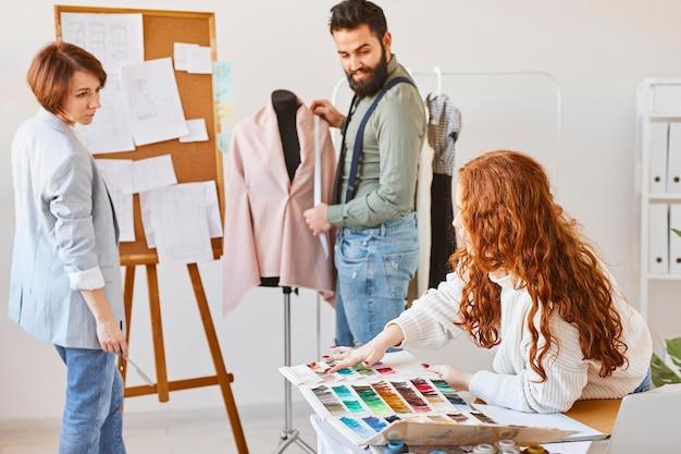 Modeontwerpers werken in atelier met kledingvorm en kleurenpalet