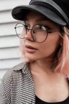 Modeportret in de buitenlucht van een vrij jong tienermeisje met een stijlvolle bril en een hoed in een casual plaidoverhemd op een houten achtergrond