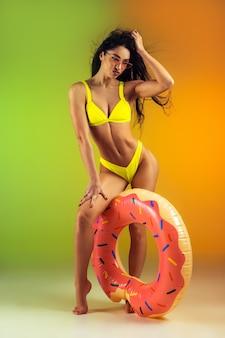 Modeportret van een jonge, fitte en sportieve vrouw met rubberen donut in stijlvolle gele badkleding op een gradiëntmuur