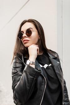 Modeportret van een mooi stedelijk hipstermeisje met zonnebril in een trendy zwart leren jack met een horloge op een grijze achtergrond in de stad