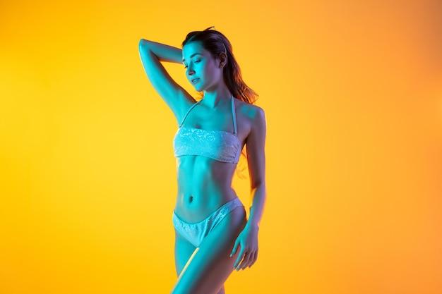 Modeportret van meisje in stijlvolle badkleding, neonlicht