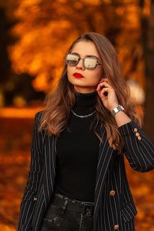 Modeportret van mooie stijlvolle vrouw met coole zonnebril in blazer en trui met ketting in park met feloranje herfstgebladerte