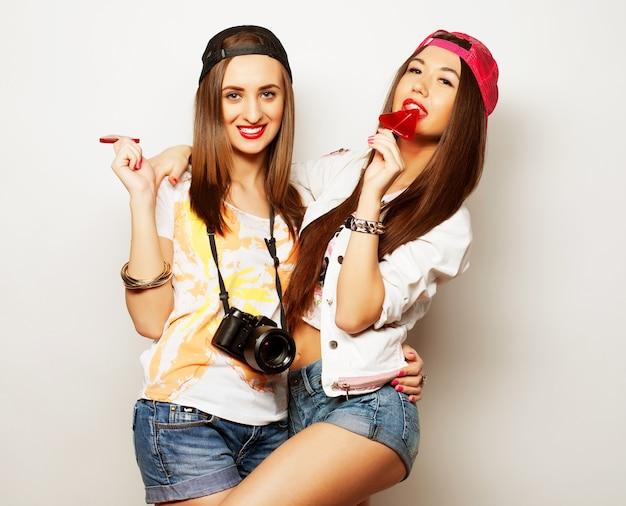 Modeportret van twee jonge mooie hipstermeisjes die lichte make-up dragen en snoepjes vasthouden. studioportret van twee vrolijke beste vriendenzussen die plezier hebben en grappige gezichten trekken.