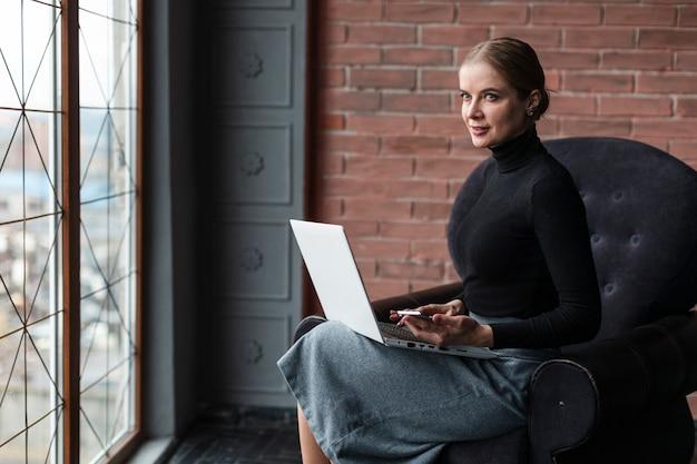 Moder vrouw die op laptop werkt