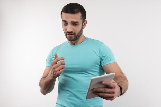 Modern apparaat. aardige knappe man met een tablet terwijl hij naar het scherm kijkt
