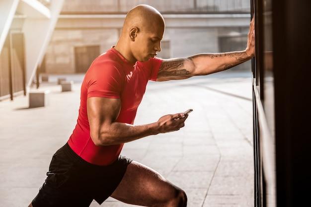 Modern apparaat. aardige serieuze man kijkt naar zijn smartphone tijdens het doen van een lichamelijke oefening