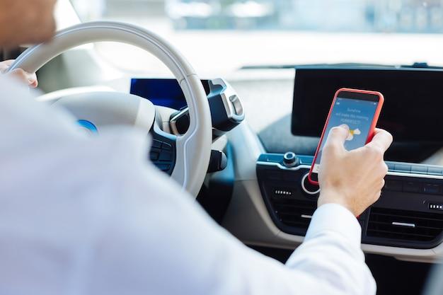 Modern apparaat. slimme aardige man met zijn smartphone tijdens het rijden in de auto