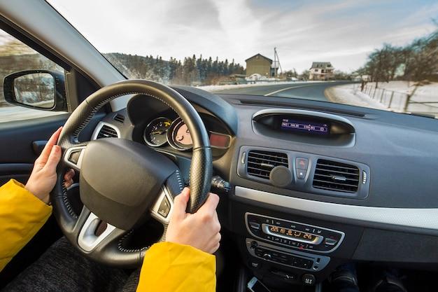 Modern autobinnenland met bestuurders vrouwelijke handen op stuurwiel, de winter sneeuwlandschap buiten. veilig rijconcept.