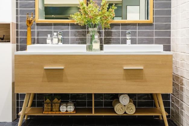 Modern badkamersbinnenland in voorgrond van tegen hoogste wasbak die natuurlijke materialen gebruikt.