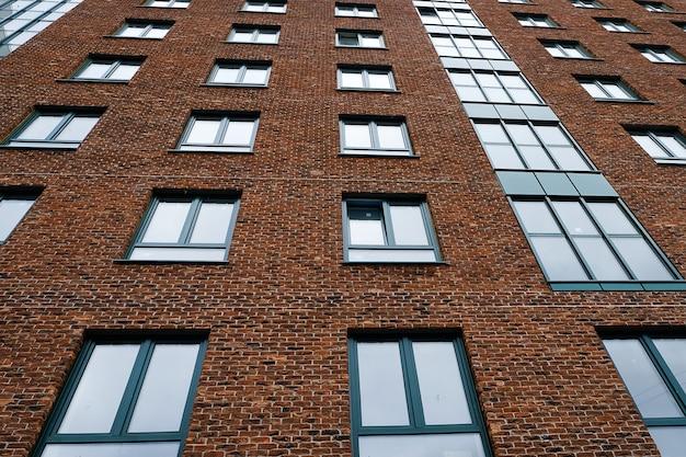Modern bakstenen gebouw met meerdere verdiepingen met windows. uiterlijk van de geconstrueerde structuur.