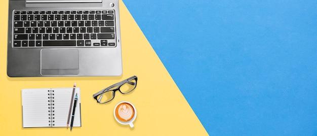 Modern bureaubureau met laptop, notitieboekje, oogglazen en hete koffie met exemplaarruimte