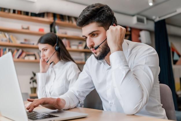 Modern callcenter met diverse jonge dispatchers op kantoor