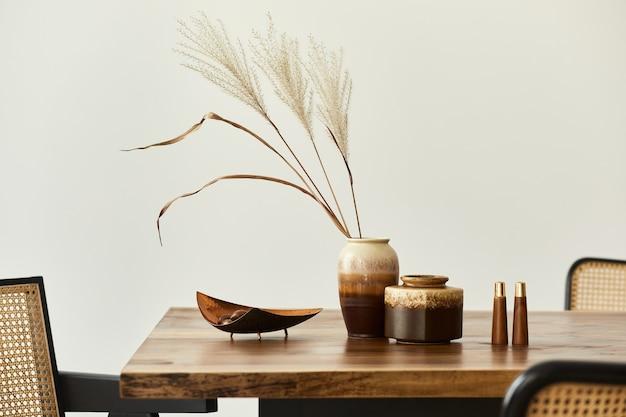 Modern concept van eetkamer interieur met houten tafel, stoelen, bord met noten, zout en peper shaker en gedroogde bloem in vaas. witte muur. details.