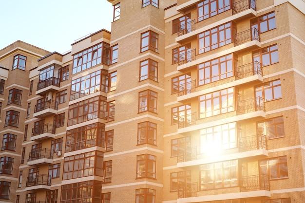 Modern condominium dat onroerend goed bouwt in de stad met blauwe lucht, zonlicht