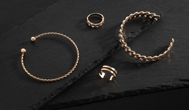 Modern design gouden glanzende armbanden en ringen op zwarte stenen platen