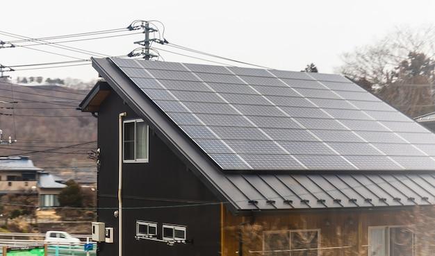 Modern eco groen huisconcept, klein huisdak met zonnecellenpanelen bovenop