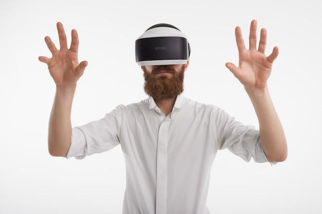 Modern futuristisch technologie en levensstijlconcept. portret van onherkenbare jonge man met dikke gemberbaard met behulp van 3d-bril, visuele realiteit ervaren, emotioneel gebaren