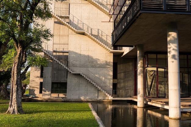 Modern gebouw exterieur architectuur met buitentrap in de buurt van boomtuin en reflectie op watervijver bij zonsondergang. luxe design met groene omgeving.