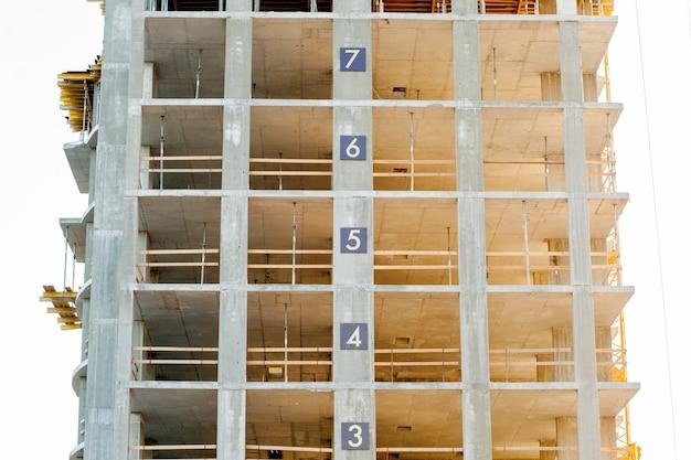 Modern gebouw in aanbouw detail, betonnen frame, raamopeningen en steigers.