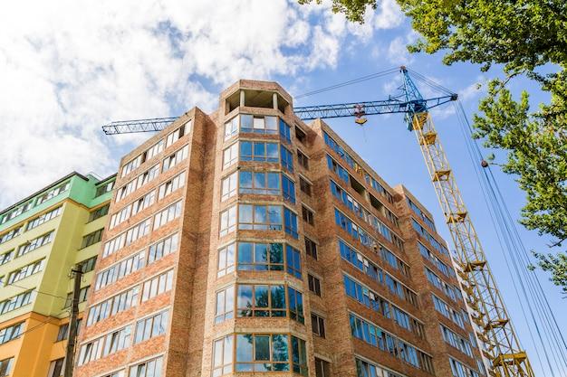 Modern gebouw met hoge verdiepingen in aanbouw met torenkraan en groene boom
