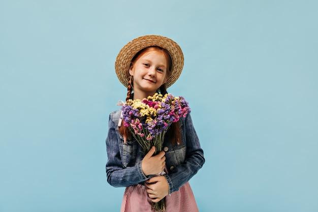 Modern gemberharig meisje in denim cool jasje, roze jurk en stro stijlvolle hoed glimlachend en met prachtige wilde bloemen op blauwe muur