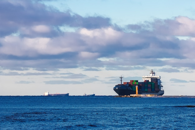 Modern grijs containerschip dat zich in stilstaand water beweegt