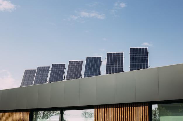 Modern huis met fotovoltaïsche zonnecellen op het dak voor alternatieve energieproductie