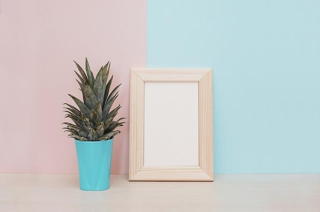 Modern huisdecor bespotten omhoog houten fotokader, vaas en tropische installatie op roze blauwe backgro