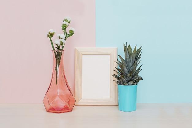 Modern huisdecor met gouden mock-up fotolijst, vaas en tropische plant op roze blauwe rug